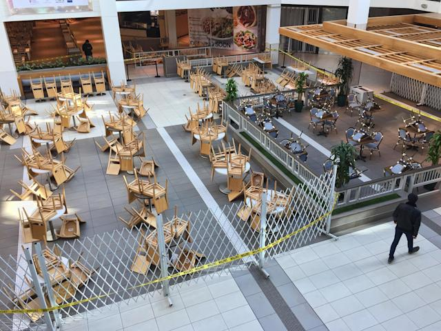 Lone man walks past chairs and tables in an empty food court in a shopping mall in Toronto, Ontario, Canada on March 21, 2020. Restaurants have been prohibited from allowing dine-in service and food courts and cafeterias have been ordered to be closed by the Province of Ontario, with any deciding to remain open facing steep fines and penalties. Retailers in malls across Canada have shuttered their stores due to the novel coronavirus (COVID-19) outbreak. Many malls are limiting entry to only 50 visitors at a time. (Photo by Creative Touch Imaging Ltd./NurPhoto via Getty Images)