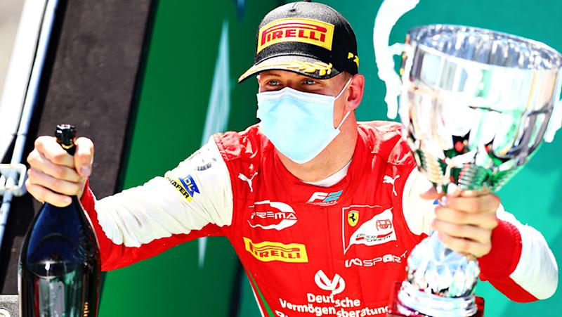Mick Schumacher is pictured holding the trophy and champagne after winning the F2 feature race at Monza.