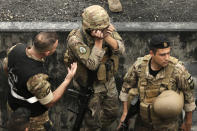FILE - In this October 23, 2019 file photo, a Lebanese army soldier, center, is overcome by emotions during scuffles between anti-government protesters and Lebanese army soldiers during a protest in the town of Jal el-Dib north of Beirut, Lebanon. The currency collapse has wiped out the salaries of the U.S.-backed Lebanese military, placed unprecedented pressure on the army's operational capabilities with some of the highest attrition rates over the past two years, and raised concerns about its ability to continue playing a stabilizing role while sectarian tensions and crime are on the rise.(AP Photo/Hassan Ammar, File)