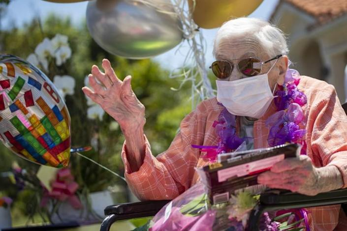 """Mildred Stratton waves to a caravan of cars led by the Alhambra police and fire departments parading past her home, celebrating her 102nd birthday on May 20 in Alhambra. <span class=""""copyright"""">(Allen J. Schaben / Los Angeles Times)</span>"""