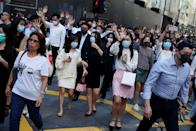Office workers shout slogans as they attend a lunchtime anti-government protest in the Central district of Hong Kong