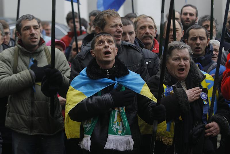 """Pro-European Union activists sing the national anthem during a rally outside the office of the richest man of Ukraine Rinat Akhmetov during an anti-government protest in Kiev, Ukraine, Wednesday, Dec. 18, 2013. Russian President Vladimir Putin and Ukranian President Viktor Yanukovych both pledged Tuesday, Dec. 17, 2013 to boost economic and trade ties to expand the """"strategic partnership"""" between the two neighbors. (AP Photo/Sergei Grits)"""
