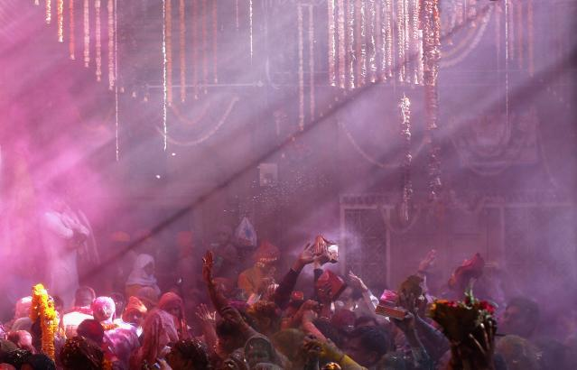 Coloured beam of rays are seen as Hindu priests (unseen) throw coloured powder at the devotees during Holi celebrations at Bankey Bihari temple in Vrindavan, in the northern Indian state of Uttar Pradesh, March 13, 2014. Holi, also known as the Festival of Colours, heralds the beginning of spring and is celebrated all over India. REUTERS/Ahmad Masood (INDIA - Tags: SOCIETY RELIGION)