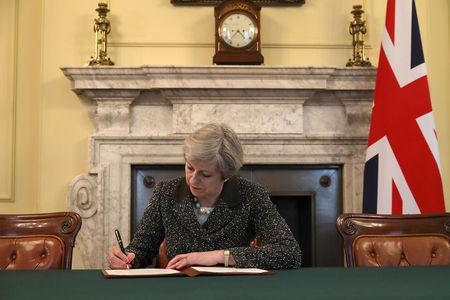 British Prime Minister Theresa May in the cabinet office signs the official letter to European Council President Donald Tusk invoking Article 50 and the United Kingdom's intention to leave the EU on March 28, 2017 in London, England. REUTERS/Christopher Furlong/Pool