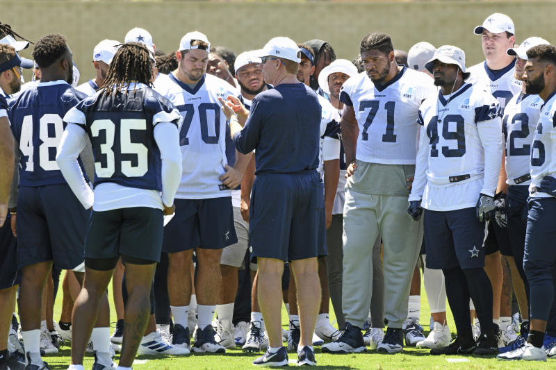 Dallas Cowboys head coach Jason Garrett, center, talks with his players during practice at the NFL football team's training camp in Oxnard, Calif., Saturday, July 27, 2019. (AP Photo/Michael Owen Baker)