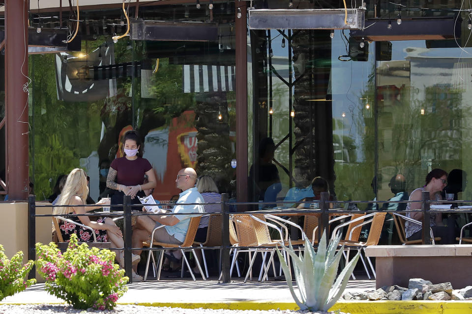 FILE - In this May 13, 2020 file photo guests dine in-house at a restaurant in Phoenix. As coronavirus cases continue to surge in Arizona, the governor shows no signs of tightening restrictions such as forcing the use of face masks. (AP Photo/Matt York,File)