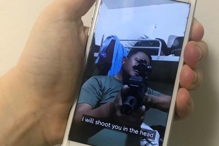 A mobile phone shows a picture of a Myanmar man in an army shirt threatening to shoot anti-coup protesters, in Singapore