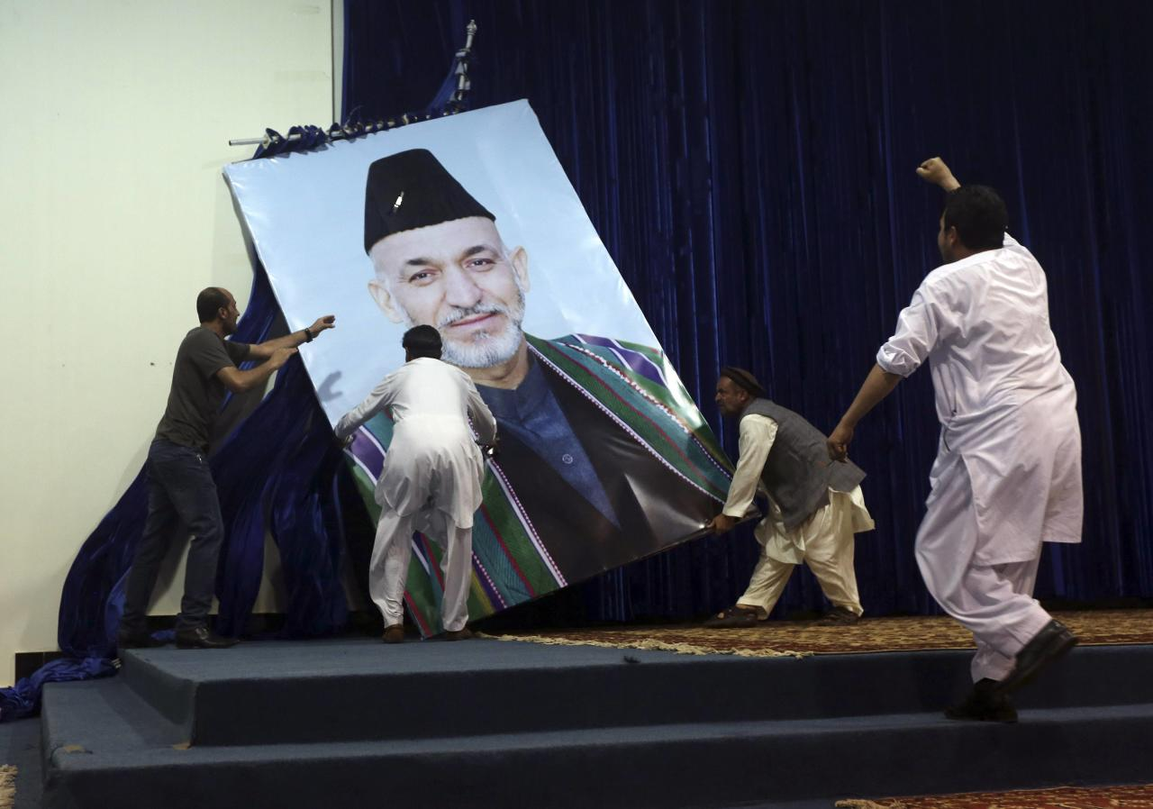 Supporters of Afghan presidential candidate Abdullah Abdullah take down a large portrait of Afghan President Hamid Karzai before a gathering in Kabul July 8, 2014. Abdullah told thousands of supporters on Tuesday he was the winner of last month's run-off election, putting himself on a collision course with his arch-rival, Ashraf Ghani. REUTERS/Omar Sobhani (AFGHANISTAN - Tags: POLITICS ELECTIONS TPX IMAGES OF THE DAY)