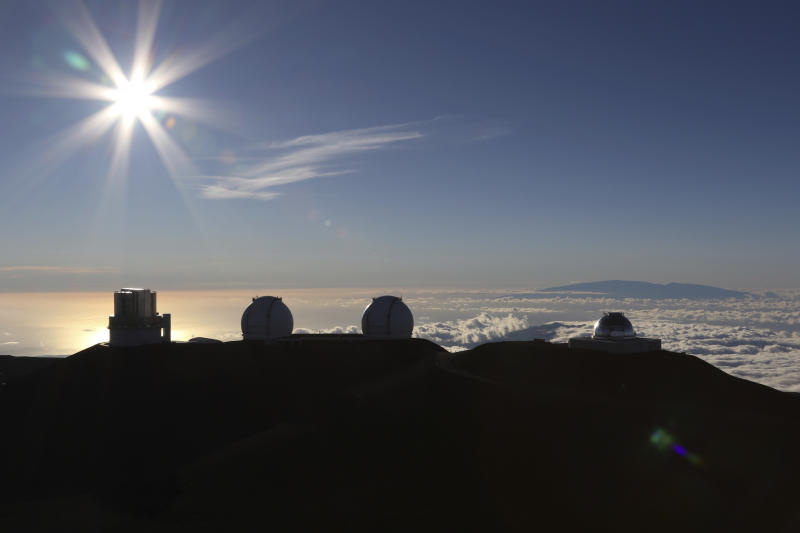 The sun sets behind telescopes at the summit of Mauna Kea, Hawaii's tallest mountain, Sunday, July 14, 2019. Hundreds of demonstrators gathered at the base of Hawaii's tallest mountain to protest the construction of a giant telescope on land that some Native Hawaiians consider sacred. State and local officials will try to close the road to the summit of Mauna Kea Monday morning to allow trucks carrying construction equipment to make their way to the top. Officials say anyone breaking the law will be prosecuted. Protestors have blocked the roadway during previous attempts to begin construction and have been arrested. (AP Photo/Caleb Jones)