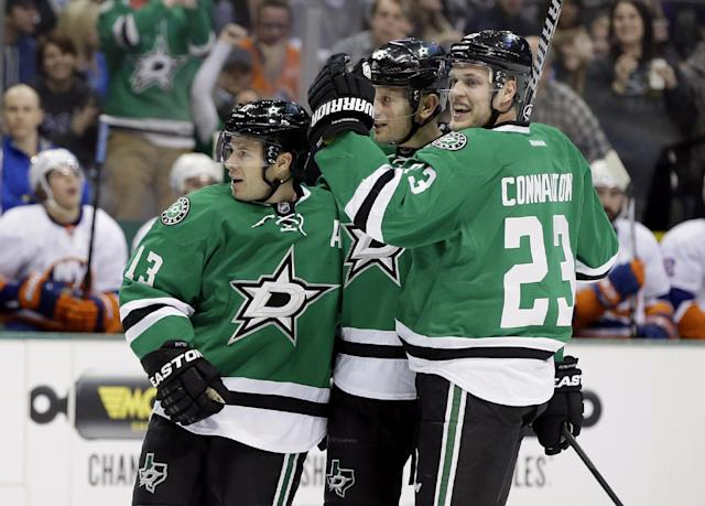 Dallas Stars' Ray Whitney (13), Sergei Gonchar, center, and Kevin Connauton (23) celebrate a goal by Whitney against the New York Islanders in the first period of an NHL hockey game, Sunday, Jan. 12, 2014, in Dallas. (AP Photo/Tony Gutierrez)