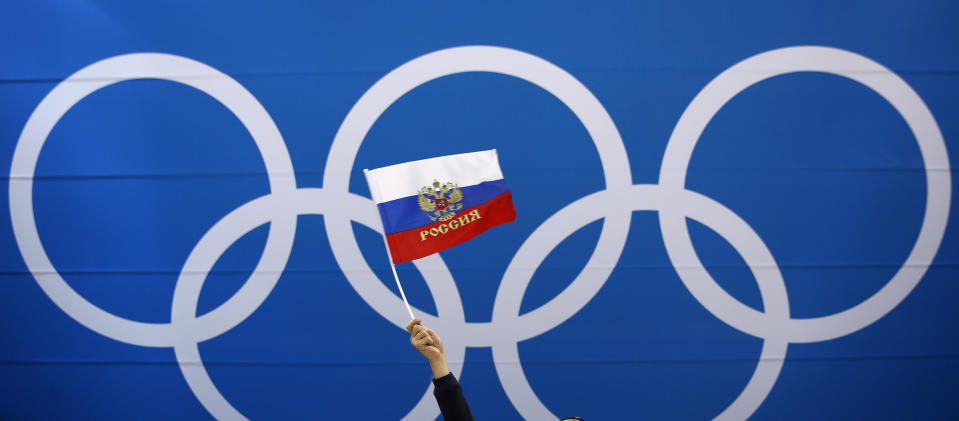 FILE - In this Wednesday, Feb. 21, 2018 file photo a fan waves a flag of Russia before the quarterfinal round of the men's hockey game between Norway and the team from Russia at the 2018 Winter Olympics in Gangneung, South Korea. The ruling on whether Russia can keep its name and flag for the Olympics will be announced on Thursday Dec. 17, 2020. The Court of Arbitration for Sport said Wednesday that three of its arbitrators held a four-day hearing last month in the dispute between the World Anti-Doping Agency and its Russian affiliate, known as RUSADA. (AP Photo/Jae C. Hong, File)