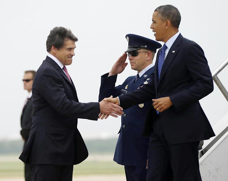 President Barack Obama, right, is greeted by Texas Gov. Rick Perry, left, during his arrival on Air Force One at Austin-Bergstrom International Airport, Thursday, May 9, 2013 in Austin, Texas. (AP Photo/Pablo Martinez Monsivais)