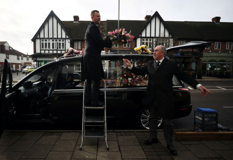 Funeral conductor Spencer Baxter and pallbearer Doug Austin from W. Uden & Sons Family Funeral Directors prepare a hearse ahead of a funeral in Bromley, amid the coronavirus disease (COVID-19) pandemic, in south east London