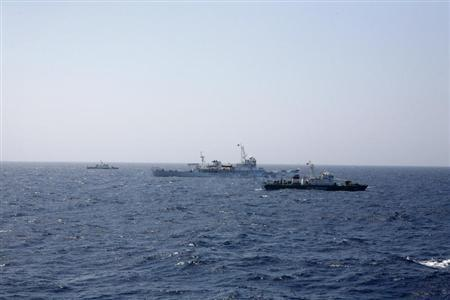 Two Vietnamese Marine Guard ships flank a Chinese coast guard vessel on the South China Sea