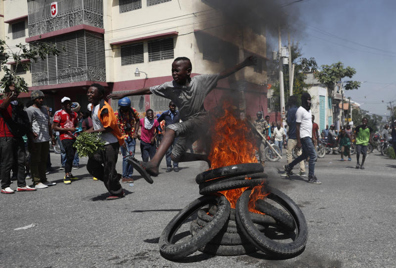 A child jumps over a burning barricade during anti-government protests in Port-au-Prince, Haiti, Friday, Oct. 11, 2019. Protesters burned tires and spilled oil on streets in parts of Haiti's capital as they renewed their call for the resignation of President Jovenel Moïse just hours after a journalist was shot to death. (AP Photo/Rebecca Blackwell)