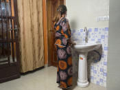 """Anifa stands in her home in the eastern Congo town of Goma on Friday, March 5, 2021. In 2019, World Health Organization Dr. Boubacar Diallo, of Canada, met her when she was working in an Ebola treatment center in Beni, eastern Congo. She said Diallo told her: """"How can a beautiful girl like you work here, testing people's temperatures and washing their hands? That's terrible."""" She said he offered her another job at five times more than her current salary where """"the conditions were very simple,"""" according to him. She rejected Diallo's offer, saying that """"if he hires me after sleeping with him...I would be a sex slave, not a WHO employee."""" Diallo rejected those claims outright. (AP Photo/Kudra Maliro)"""