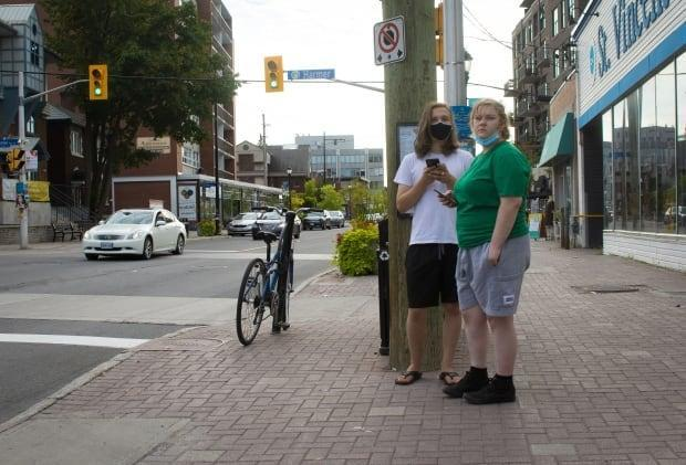 Two people wait at a bus stop on Wellington Street West in Ottawa on Aug. 27, 2021, during the COVID-19 pandemic. (Trevor Pritchard/CBC - image credit)