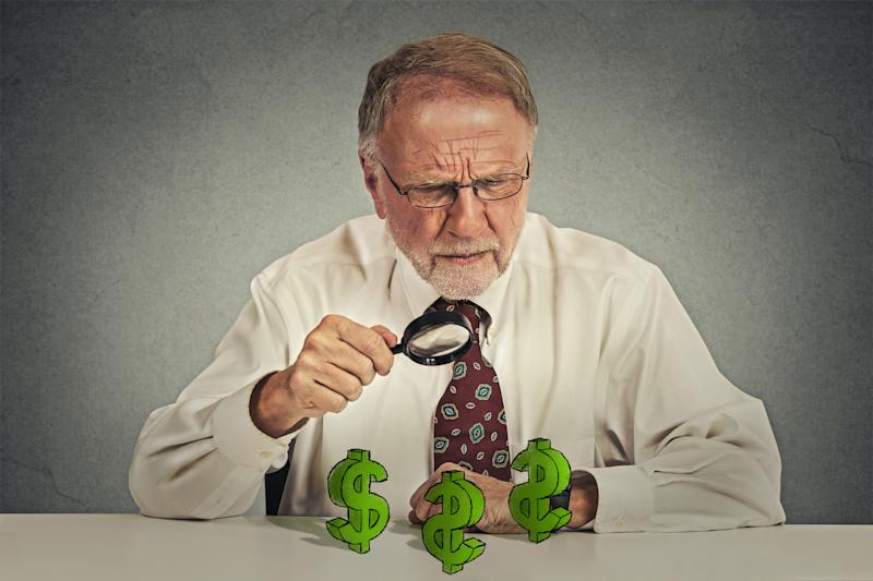 A senior man holding a magnifying glass while examining dollar signs on the counter in front of him.