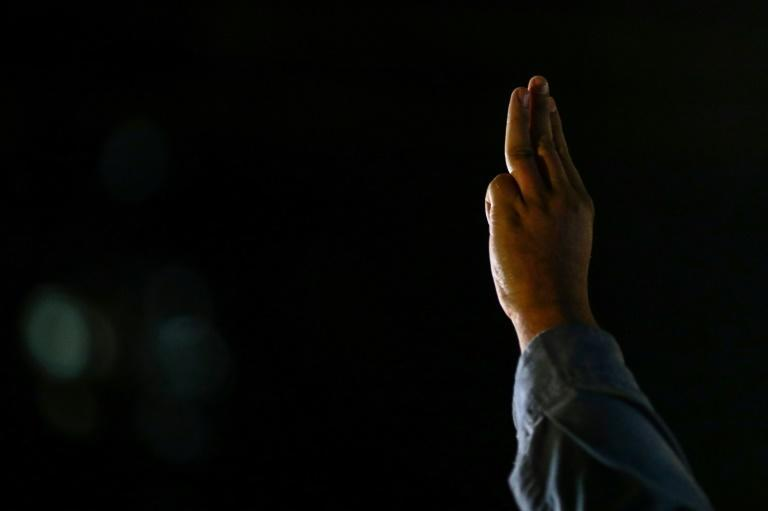A Thai pro-democracy protester gives the three-finger salute outside the Prachachuen police station in Bangkok