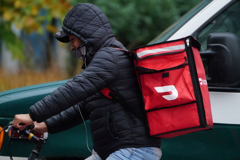 FILE PHOTO: A delivery person for Doordash rides his bike in the rain during the coronavirus disease (COVID-19) pandemic in the Manhattan borough of New York City