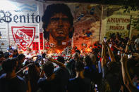 FILE - In this Nov. 25, 2020 file photo, soccer fans hold a vigil for Diego Maradona outside the stadium of Argentinos Juniors soccer club, where he started as a professional footballer, in La Plata, Buenos Aires, Argentina, amid the new coronavirus pandemic. Large gatherings of people that defied social distancing guidance may have helped spread the virus at the end of 2020. (AP Photo/Marcos Brindicci, File)