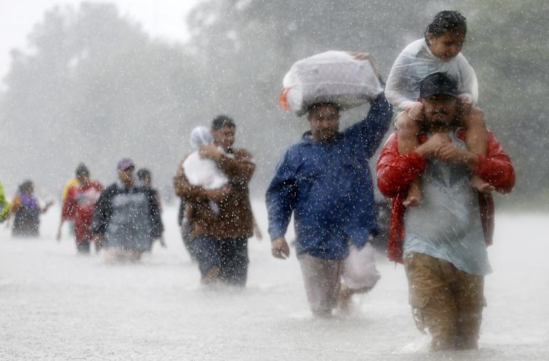 Residents wade through flood waters from in Beaumont Place, Houston, on Monday. (Jonathan Bachman/Reuters)