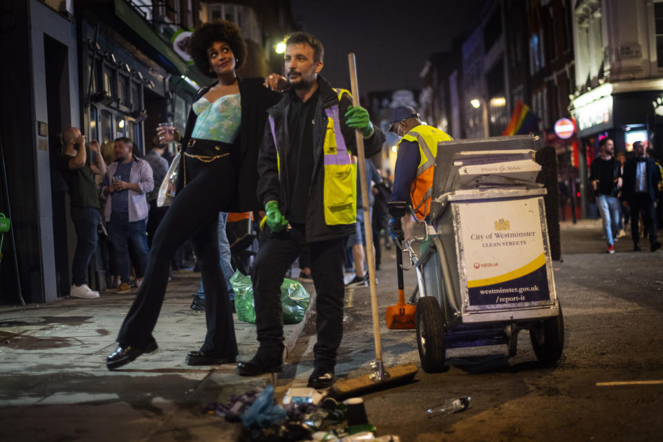 A woman poses with a street cleaner in Soho as late-night drinkers continue into the early hours of Sunday morning as coronavirus lockdown restrictions are eased across England, Sunday July 5, 2020. (Victoria Jones/PA via AP)