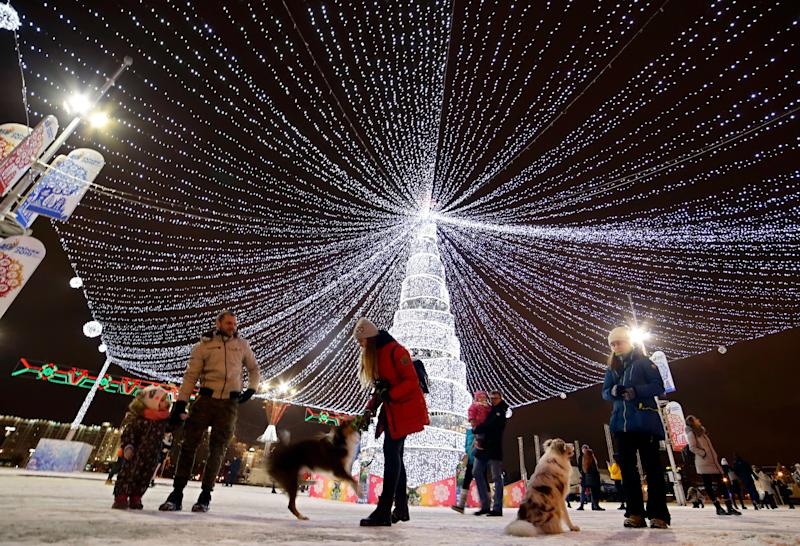 People play with their dogs next to a New Year tree standing on a square and decorated to mark the upcoming Christmas and New Year celebrations in Minsk, Belarus, Tuesday, Dec. 18, 2018. (AP Photo/Sergei Grits)