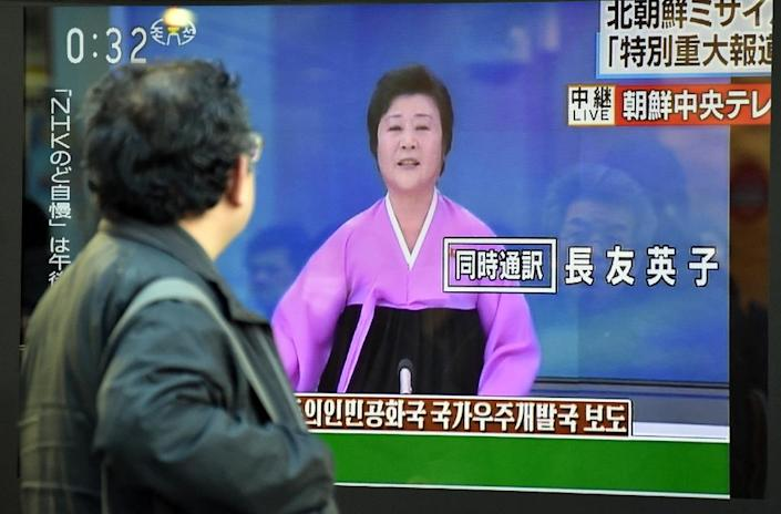 A pedestrian looks at a television screen showing the Korean Central Television special broadcast on North Korea's rocket launch, in Tokyo on February 7, 2016 (AFP Photo/Kazuhrio Nogi)