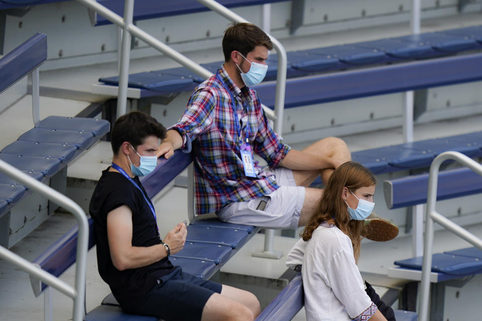 Spectators watch from the stands in protective masks at the Western & Southern Open tennis tournament, Saturday, Aug. 22, 2020, in New York. (AP Photo/Frank Franklin II)