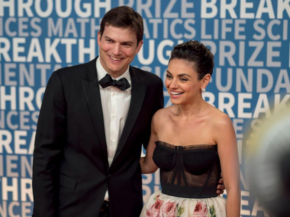 Ashton Kutcher with his arm around Mila Kunis on the red carpet in front of a blue step-and-repeat.