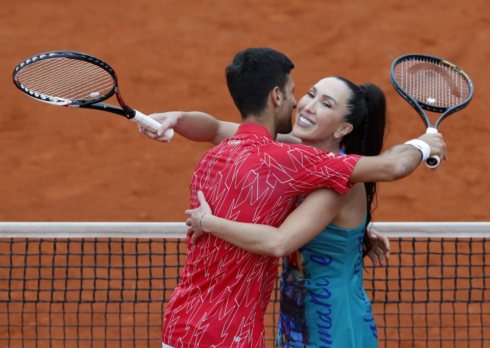 Serbia's Novak Djokovic, left, celebrates with Jelena Jankovic after a tennis doubles match against Serbia's Nenad Zimonjic and Olga Danilovic during the Adria Tour charity tournament, in Belgrade, Serbia, Friday, June 12, 2020. Serbian tennis player Novak Djokovic set up a series of tennis tournaments in the Balkan region while the sport is suspended amid the coronavirus pandemic. (AP Photo/Darko Vojinovic)