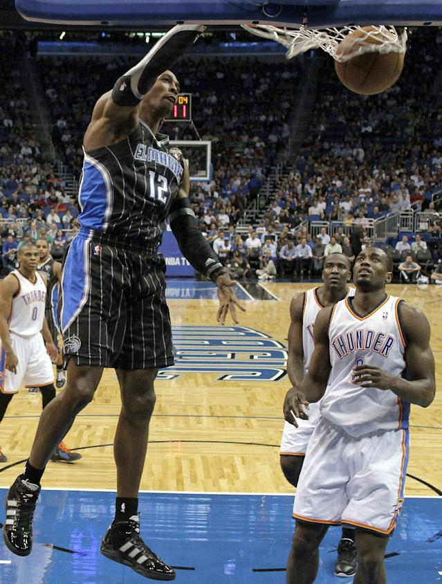 Orlando Magic's Dwight Howard (12) dunks the ball in front of Oklahoma City Thunder's Serge Ibaka during the first half of an NBA basketball game Thursday, March 1, 2012, in Orlando, Fla. (AP Photo/John Raoux)
