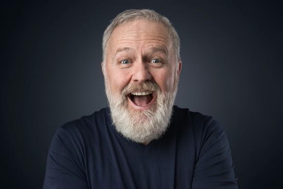 Bearded older man with big smile.