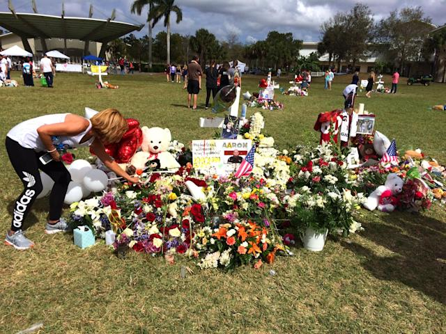 <p>A woman places a rose at a makeshift memorial for Marjory Stoneman Douglas High School shooting victim, Aaron Feis, at Pine Trail Park, Parkland, Fla., Feb. 19, 2018. (Photo: Mindy Katzman/Yahoo News) </p>