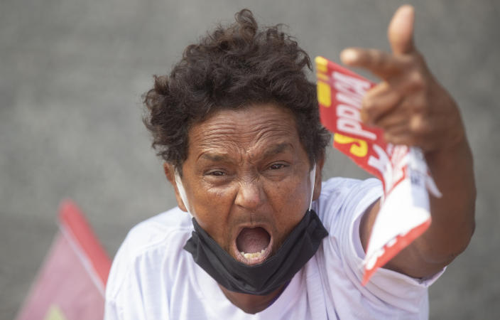 A demonstrator protests against Brazil's President Jair Bolsonaro and his handling of the new coronavirus pandemic marking May Day, or International Workers' Day, in Sao Paulo, Brazil, Saturday, May 1, 2021. (AP Photo/Andre Penner)