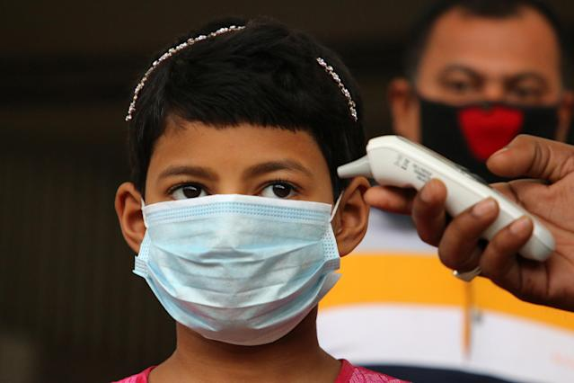 A child is pictured having his temperature read at Dhaka railway station in Bangladesh on 18 March. Bangladesh has had 14 confirmed cases. (Getty Images)