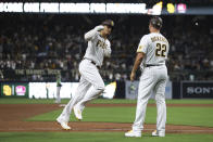 San Diego Padres' Manny Machado, left, rounds third base to greetings from Bobby Dickerson after hitting a three-run home run against the Oakland Athletics during the fifth inning of a baseball game Tuesday, July 27, 2021, in San Diego. (AP Photo/Derrick Tuskan)