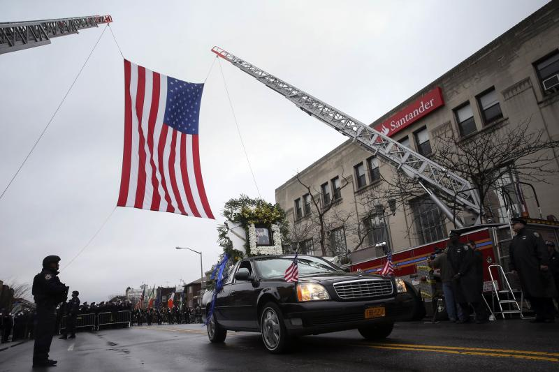 The lead funeral procession vehicle for NYPD officer Wenjian Liu makes its way under a US flag en route to the cemetery in the Brooklyn borough of New York