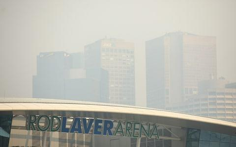 A general view of Rod Laver Arena with the city shrouded in smoke in the background ahead of the 2020 Australian Open - Credit: Getty