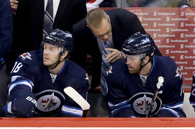 Winnipeg Jets head coach Paul Maurice talks with Bryan Little (18) and Andrew Ladd (16) during first period NHL hockey action against the Phoenix Coyotes in Winnipeg, Canada, Monday, Jan. 13, 2014. (AP Photo/The Canadian Press, Trevor Hagan)