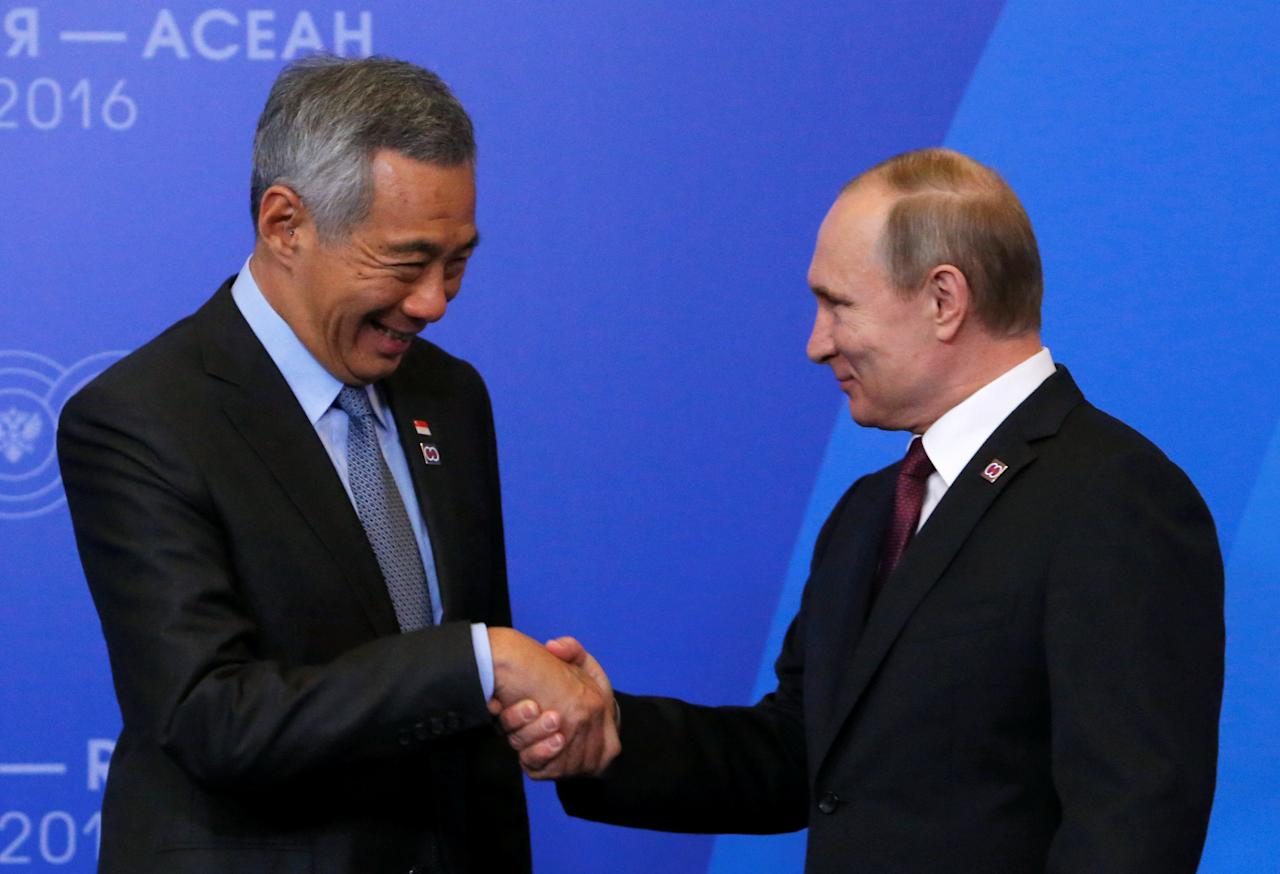 Russian President Vladimir Putin shakes hands with Singapore's Prime Minister Lee Hsien Loong during a welcoming ceremony for heads of the delegations at the Russia-ASEAN summit in Sochi, Russia, May 20, 2016. REUTERS/Sergei Karpukhin