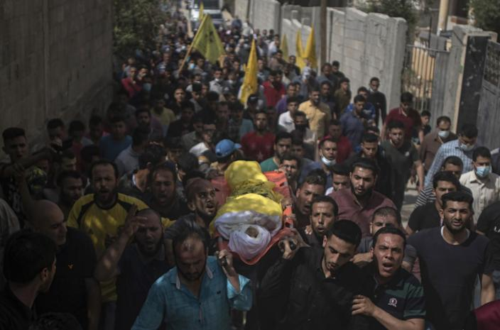 Mourners carry a body wrapped in white and yellow on a sling amid a throng of people