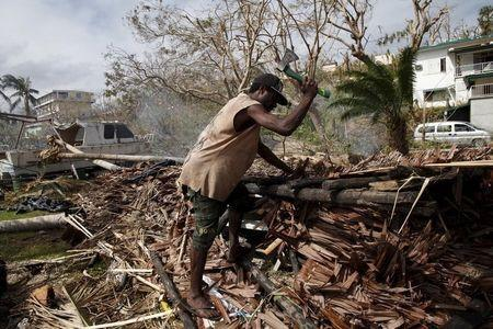 A worker chops up fallen trees next to a destroyed boat at a resident's compound days after Cyclone Pam in Port Vila, capital city of the Pacific island nation of Vanuatu March 19, 2015. REUTERS/Edgar Su