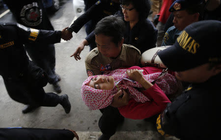 Government security officials carry a family member of passengers onboard missing AirAsia flight QZ8501 after she collapsed at a waiting area in Juanda International Airport, Surabaya, December 30, 2014.  REUTERS/Beawiharta