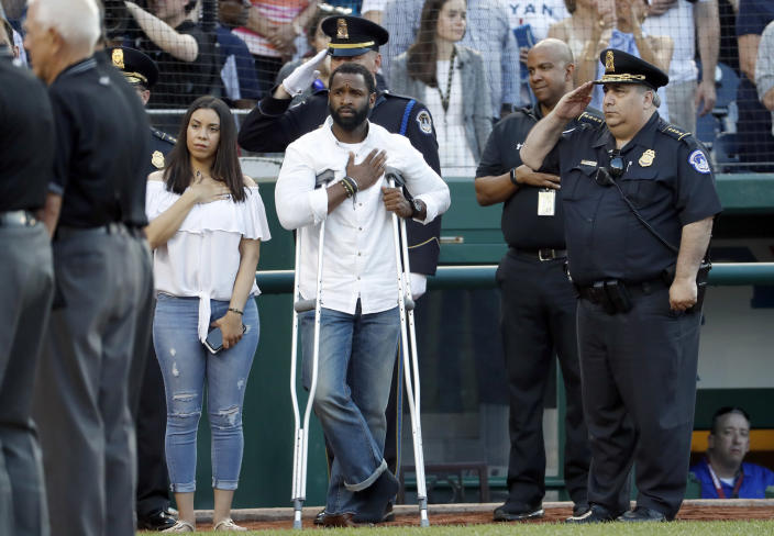 <p>Injured Capitol Hill Police officer David Bailey, center, holds his hand over his heart during the National Anthem with U.S. Capitol Police Chief Matthew Verderosa, far right, before the Congressional baseball game, Thursday, June 15, 2017, in Washington. The annual GOP-Democrats baseball game raises money for charity. (Photo: Alex Brandon/AP) </p>