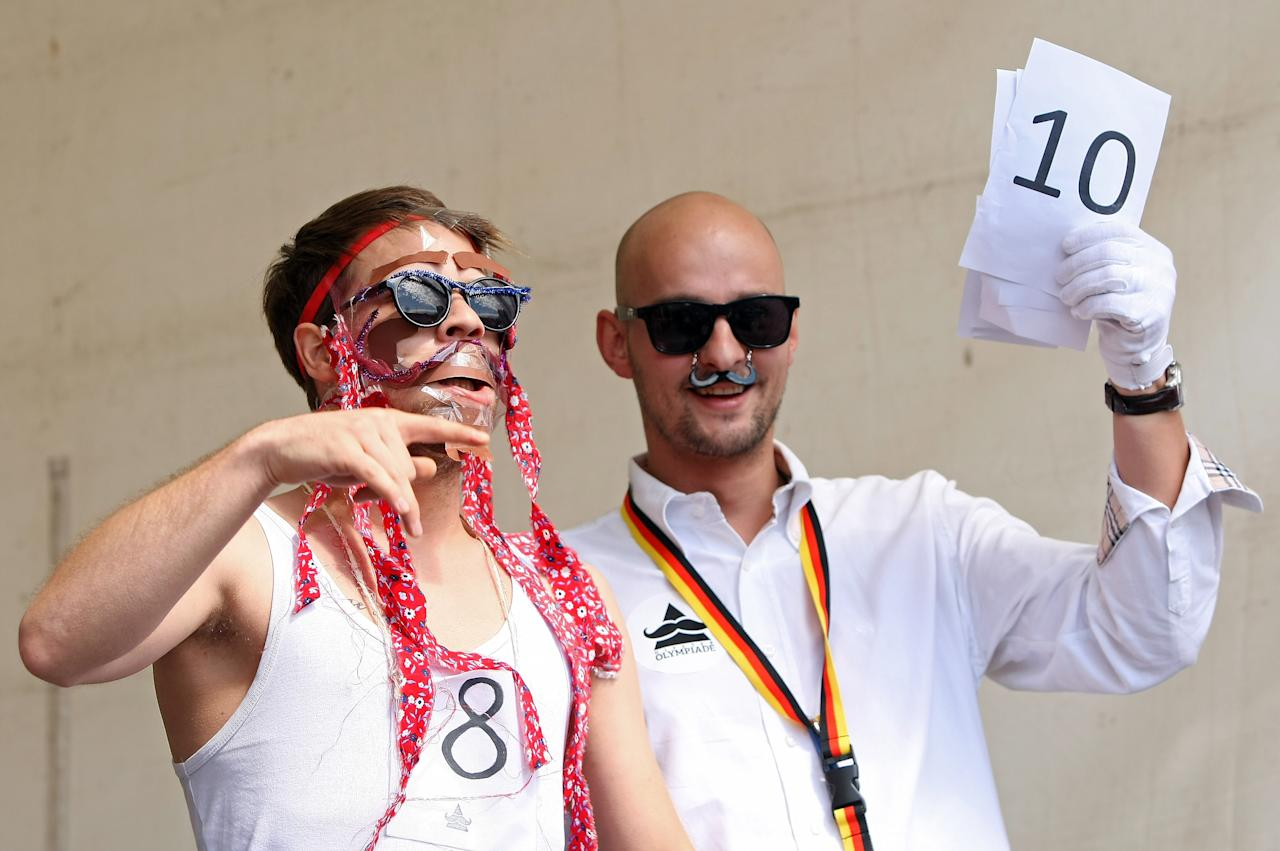 "BERLIN, GERMANY - JULY 21:  A contestant receives a judge's verdict in the make-your-own-ironic-Hipster-moustache competition at the second annual Hipster Olympics on July 21, 2012 in Berlin, Germany. With events such as the ""Horn-Rimmed Glasses Throw,"" ""Skinny Jeans Tug-O-War,"" ""Vinyl Record Spinning Contest"" and ""Cloth Tote Sack Race,"" the Hipster Olympics both mocks and celebrates the Hipster subculture, which some critics claim could never be accurately defined and others that it never existed in the first place. The imprecise nature of determining what makes one a member means that the symptomatic elements of adherants to the group vary in each country, but the archetype of the version in Berlin, one of the more popular locations for those following its lifestyle, along with London and Brooklyn, includes a penchant for canvas tote bags, the carbonated yerba mate drink Club Mate, analogue film cameras, asymetrical haircuts, 80s neon fashion, and, allegedly, a heavy dose of irony. To some in Berlin, members of the hipster ""movement"" have replaced a former unwanted identity in gentrifying neighborhoods, the Yuppie, for targets of criticism, as landlords raise rents in the areas to which they relocate, particularly the up-and-coming neighborhood of Neukoelln.  (Photo by Adam Berry/Getty Images)"
