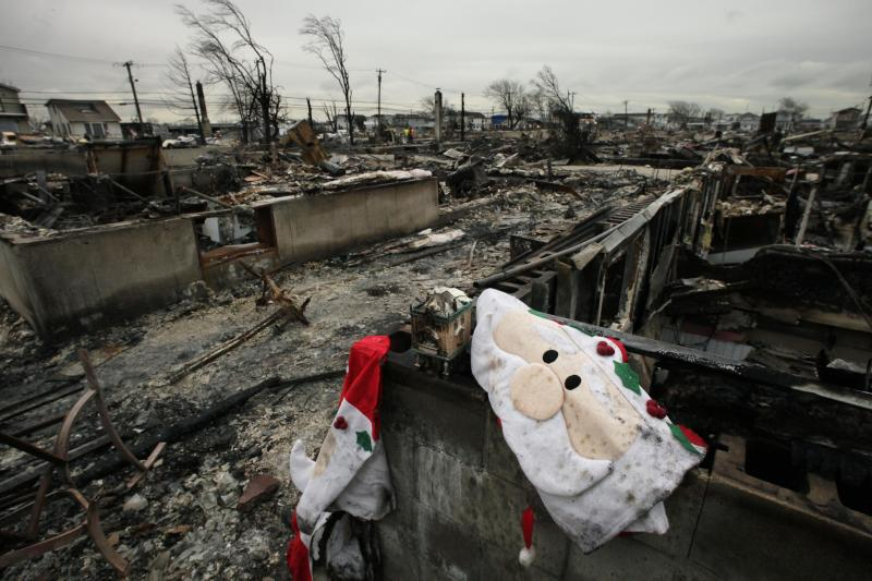 FILE - In this Nov. 13, 2012 file photo, Christmas decorations from the charred remains of a home, are shown in the Breezy Point section New York's Queens borough. More than 50 homes were lost in a fire that swept through the oceanside community during Superstorm Sandy. Some residents of New York City's storm-battered Breezy Point neighborhood say thieves looted their damaged houses over Thanksgiving. (AP Photo/Mark Lennihan)