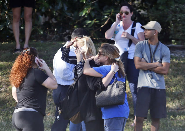 <p>Anxious family members wait for news of students as two people embrace, Wednesday, Feb. 14, 2018, in Parkland, Fla. A shooting at Marjory Stoneman Douglas High School sent students rushing into the streets as SWAT team members swarmed in and locked down the building. (Photo: Wilfredo Lee/AP) </p>