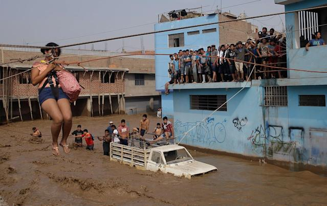 <p>MAR. 17, 2017 – A woman is pulled to safety in a zipline harness in Lima, Peru. Intense rains and mudslides over the past three days have wrought havoc around the Andean nation and caught residents in Lima, a desert city of 10 million where it almost never rains, by surprise. (Photo: Martin Mejia/AP) </p>